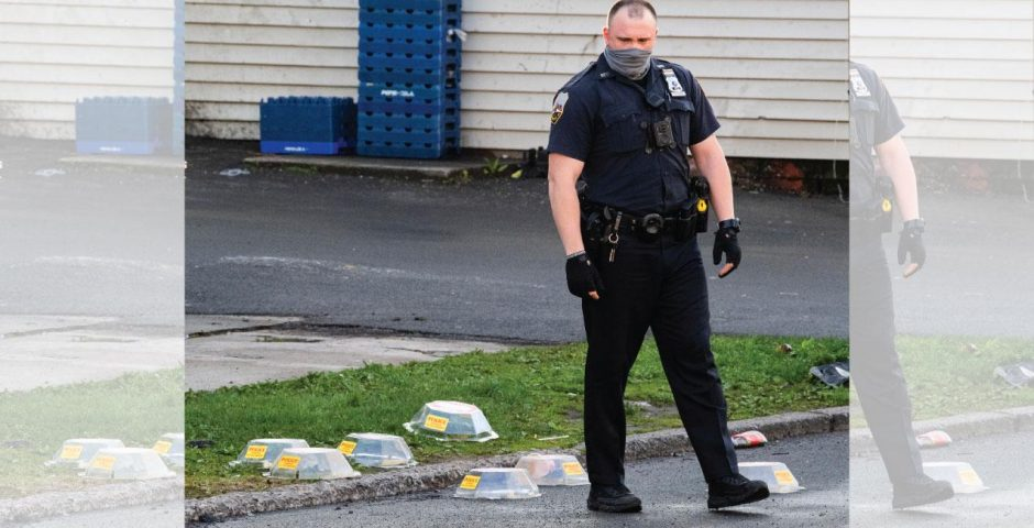 Officer Steven Flood steps in between evidence markers covering shell casings after the shooting May 1
