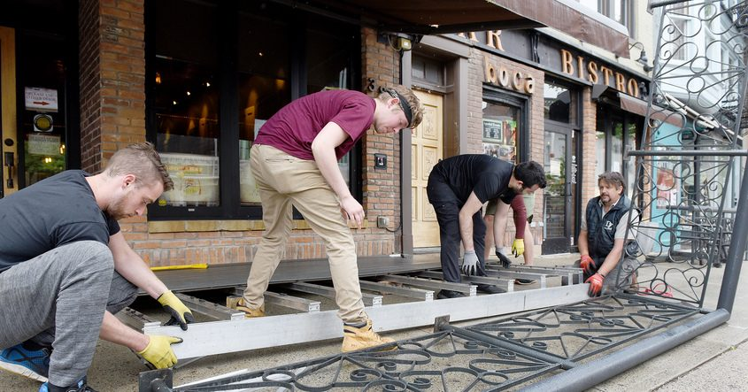 Employees ready an outdoor patio at Boca Bistro on Broadway in Saratoga Springs Tuesday for a later phase