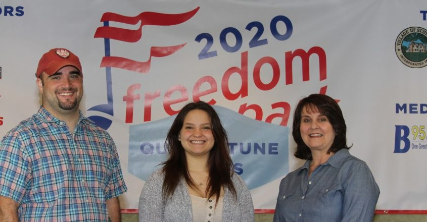 Justin Cook and Cathy Gatta of the Freedom Park Foundation flank singer Madison VanDenburg.