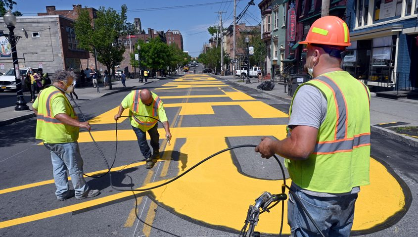 "A contract painting company stencil paints the middle of Lark St. with ""Black Lives Matter"" Tuesday"