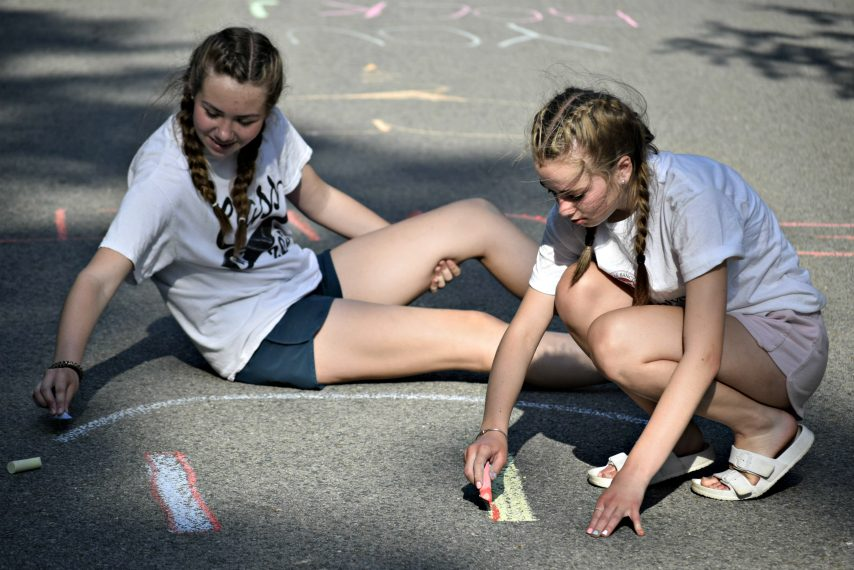 Grace Smith (left) and Ella Blanchard make chalk drawings Tuesday on Hickory Ridge Drive in Amsterdam.