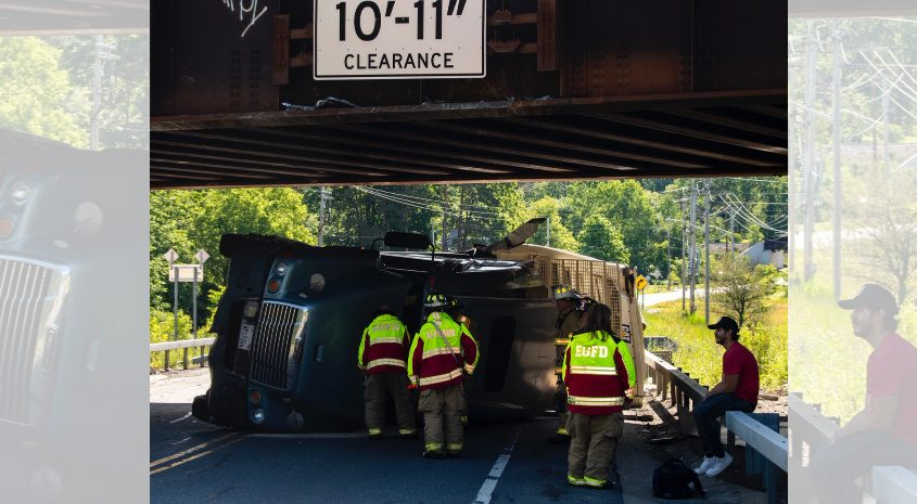 The driver of the the overturned truck Monday morning sits on the guard rail