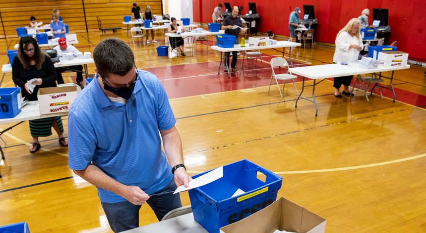 John Perreault opens school ballots in the Mont Pleasant Middle School gymnasium Tuesday