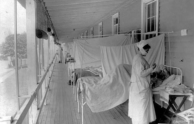 A nurse takes a patient's pulse in the influenza ward at Walter Reed Hospital, Washington, D.C. in 1918 or 1919.