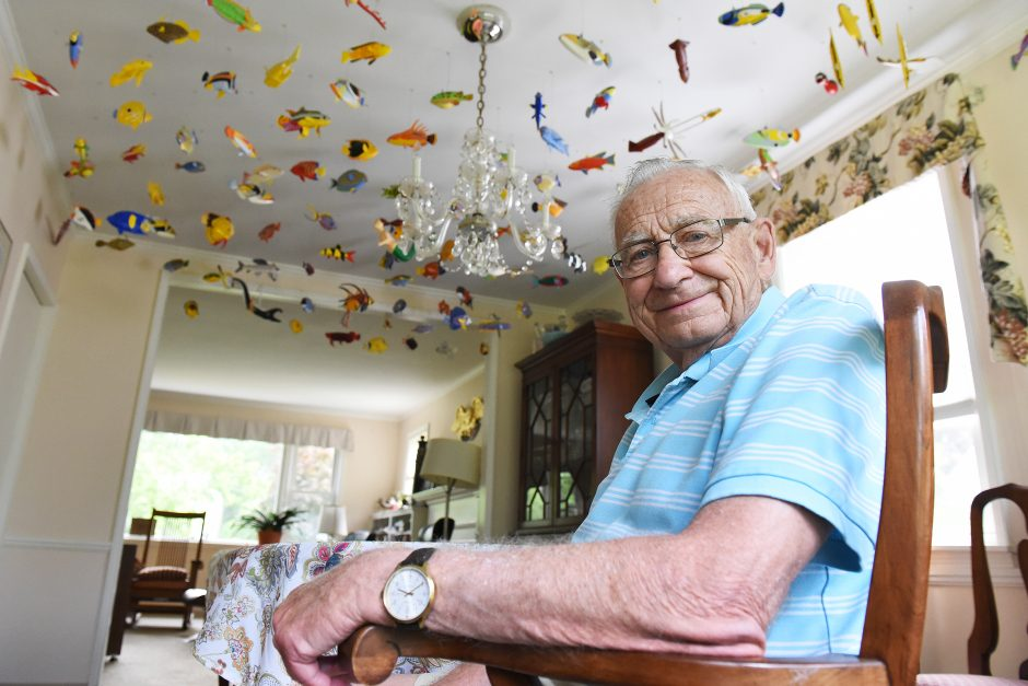 Ed Koch at his Niskayuna home, sitting under many of the wooden fish he has carved and painted.