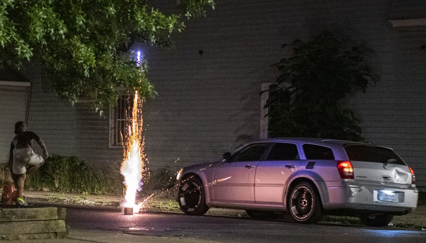A car passes an exploding firework at the intersection of Backus and Albany streets last week
