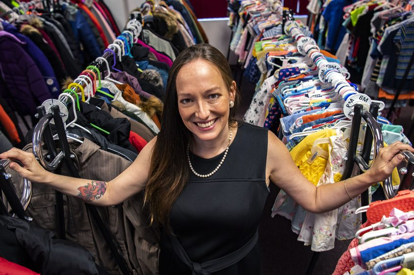 Rayn Boncie, CEO/Founder of Things of My Very Own stands among rows of coats and dresses