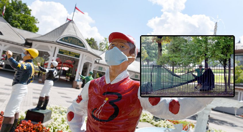 A worker installs temporary screening on the Union Ave. fence near the second turn of Saratoga Race Course.