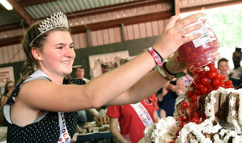 Dairy Queen Lainey Koval of Stillwater puts cherries on a giant sundae at last year's fair. A queen will again be named.