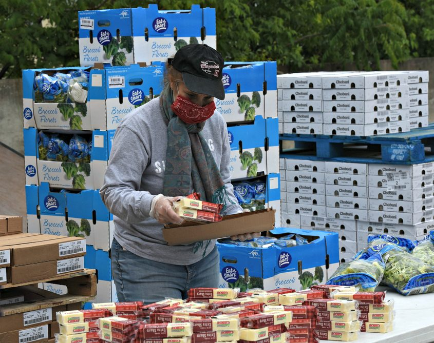 Lori Fletcher unloads cheese at a distribution event hosted by Catholic Charities and the Regional Food Bank of Northeastern NY.