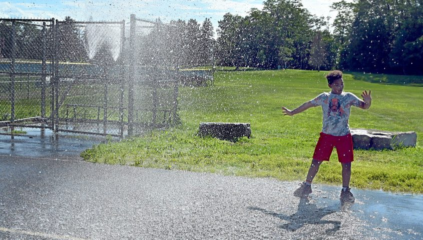 Ernesto Melly, 12, takes a break from playing basketball to run through the sprinkler Tuesday