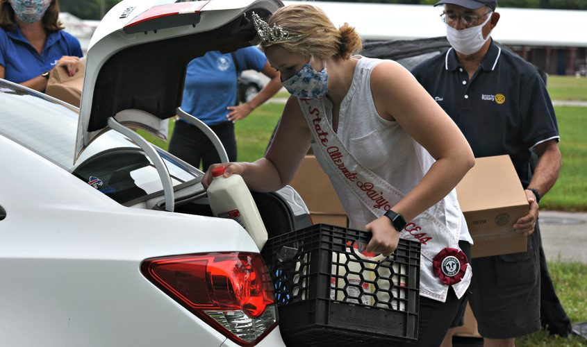 Miss New York 2nd alternate Dairy Princess, Erin Armitage puts half gallon containers of milk in the truck of a vehicle Wed.