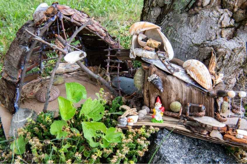 A fairy home is displayed under a tree in front of the Woodlawn Public Library in Schenectady.