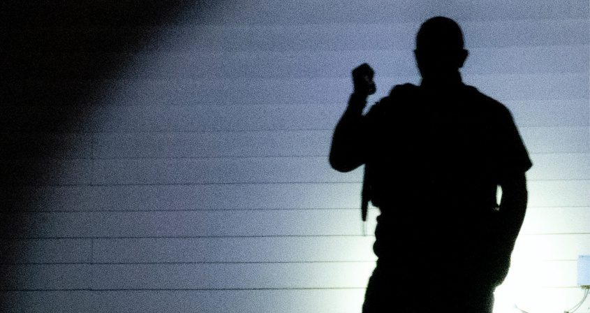 A police officer casts a shadow looking for evidence early Sunday in Schenectady