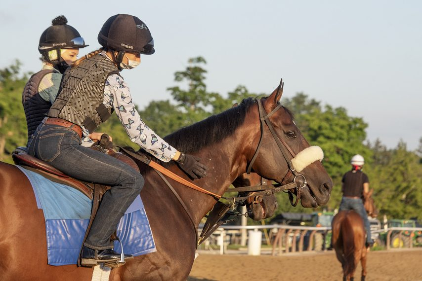 Tom's d'Etat gets a pat on the neck from exercise rider Olha Krushevska before a gallop on the Saratoga main track.
