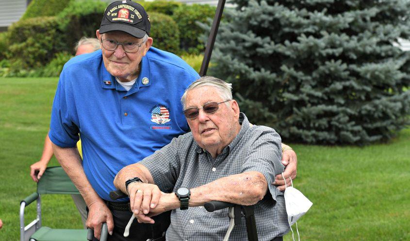 Allan Atwell, 95, seated, shares a moment with fellow veteran Charley Levesque after his drive-by parade.