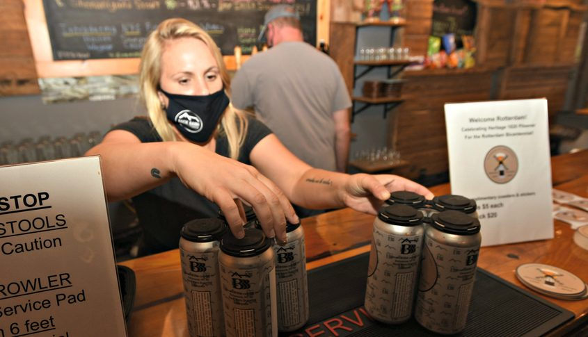 Nicole Pagano, operations manager at Back Barn Brewing places two 4-packs of Heritage 1820 pilsener on the bar Tuesday night.