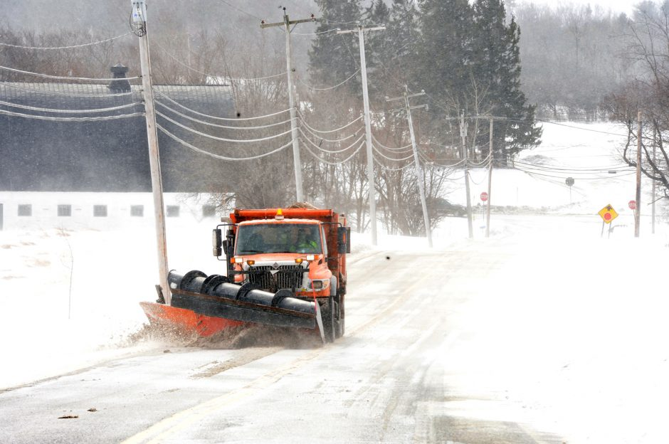 A Schenectady County snowplow knocks wind drifts off the road and spreads salt-dirt mixtures in 2019.