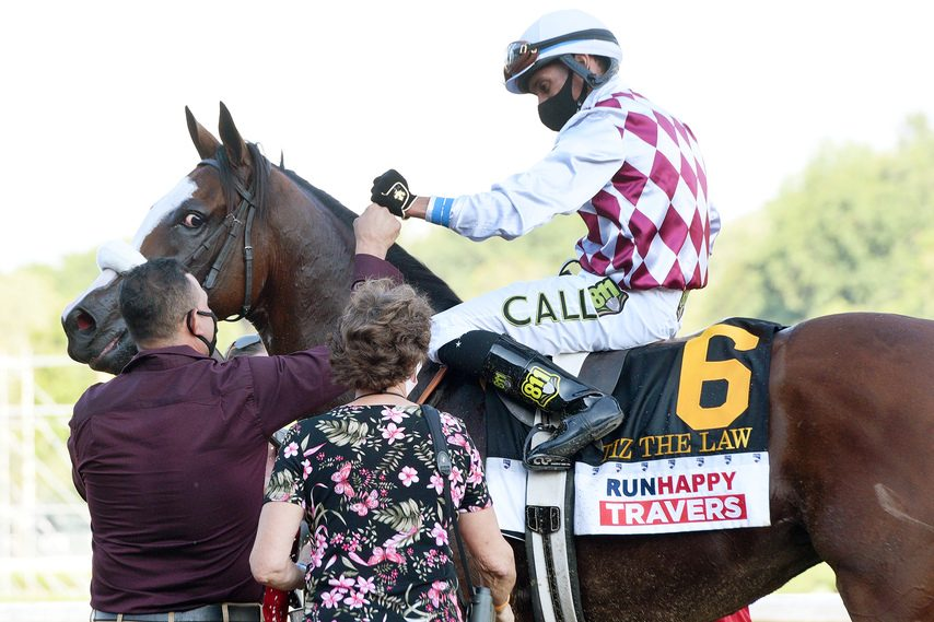 Jockey Manny Franco fist-bumps with groom Juan Barajas after Tiz the Law won the Travers on Aug. 8.