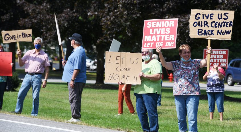 Carol Moll, of Saratoga Springs (right), holds her signs with other senior citizen members of Ballston Area Senior Center protest outside the Town of Milton Community Center in Milton on Wednesday.