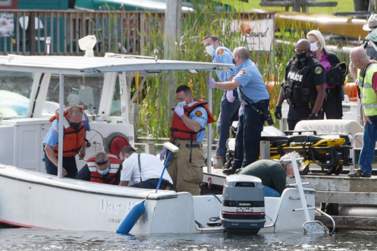 Rescuers tend to the man Wednesday on the floor of the boat as they near the dock. Credit: Erica Miller/Staff Photographer