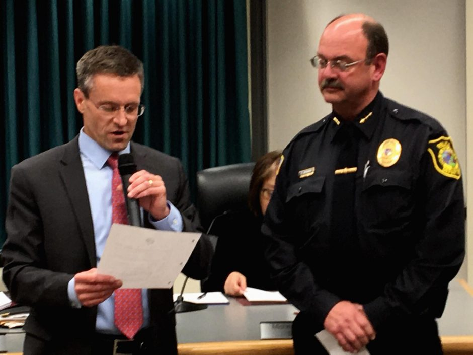 Niskayuna Councilman Bill McPartlon reads a resolution announcing town support for National Police Week in 2019 as town Police Chief Dan McManus listens.