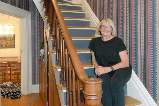 Joan Mikalson sits on a staircase at her home in the Stockade section of Schenectady.
