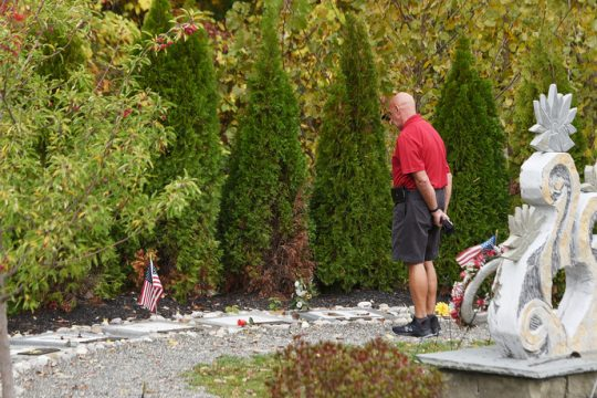 A man walks around the Schoharie limo crash memorial site Tuesday. ERICA MILLER/STAFF PHOTOGRAPHER