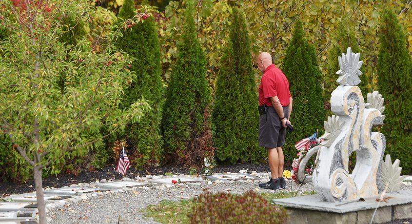 A man walks around the Schoharie limo crash memorial site Tuesday.ERICA MILLER/STAFF PHOTOGRAPHER
