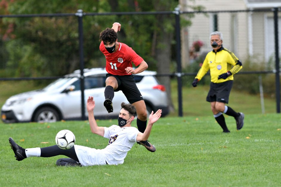Stan Hudy photoNiskayuna's Mike Puccioni gets a shot off as Troy's Robert Laviosi slides in front of him during the Suburban Council boys' soccer opener Saturday morning at Niskayuna High School.