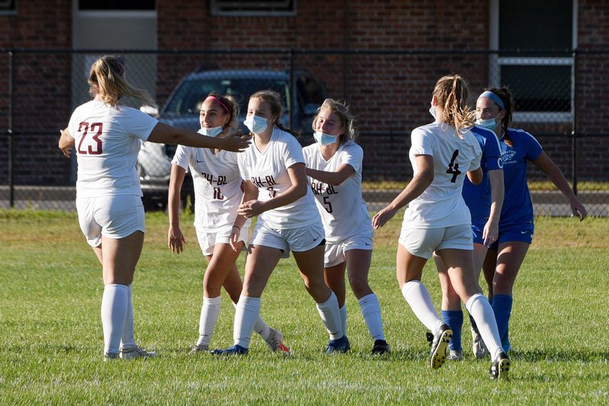 ERICA MILLER/STAFF PHOTOGRAPHER Burnt Hills-Ballston Lake teammates celebrate their second goal over Saratoga during their first soccer game of the season at SSHS in Saratoga Springs on Saturday.