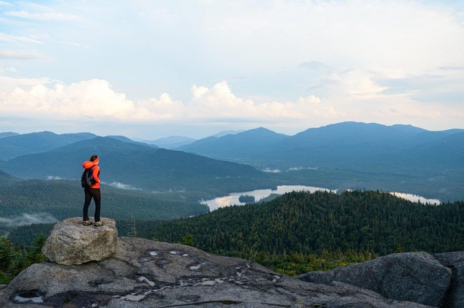 A lone hiker enjoys the view from the summit of 3,353-foot Ampersand Mountain, one of the Saranac Lake 6er hikes. Photo provided