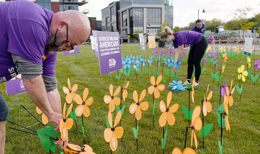 Walk to End Alzheimers with Alzheimers Association volunteer Ray Shafer, of Albany, who's father Ray Shafer of Glenville is diagnosed with Alzheimers, places a orange flower in their Promise Garden for participants to view on the road at Mohawk Harbor in Schenectady on Saturday.