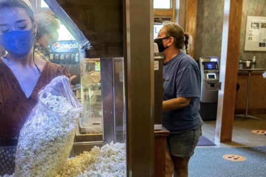"Catherine Alesio fills a bag of popcorn for a customer in the lobby of the Scotia Cinema on Aug. 14. The movie theater is offering ""€popcorn to go""€ Thursdays through Sundays as it struggles with a state-ordered shutdown."