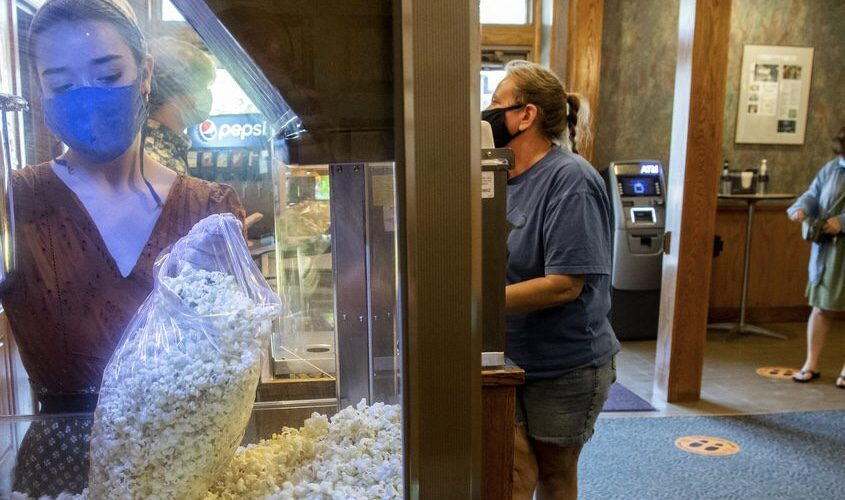 """Catherine Alesio fills a bag of popcorn for a customer in the lobby of the Scotia Cinema on Aug. 14. The movie theater is offering """"€popcorn to go""""€ Thursdays through Sundays as it struggles with a state-ordered shutdown."""