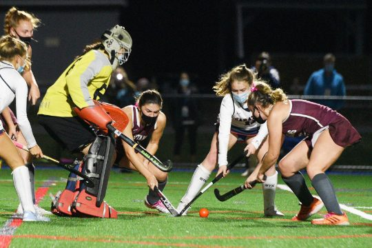 ERICA MILLER/STAFF PHOTOGRAPHER Burnt Hills-Ballston Lake's Paige Thowe, right, makes a shot with Grace Todd against Saratoga Springs goalie Emma Piccirillo and Sophie Sefransky during the first field hockey game under the lights at the Blue Streaks' new field on Friday.