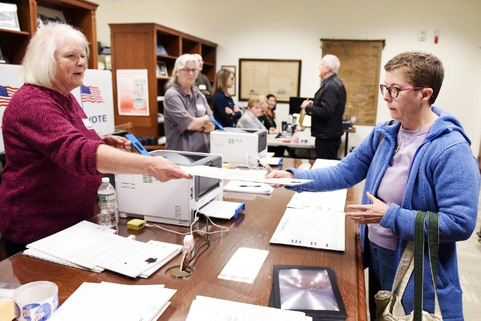 ERICA MILLER/GAZETTE PHOTOGRAPHER In this file photo from Oct. 26, 2019, Patricia Zirpoli, of Halfmoon, right, receives her individually printed ballot from election inspector Nancy D'Amico during the first early elections at Clifton Park- Halfmoon Public Library in Clifton Park.