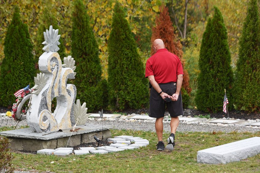 A man visits the limousine crash memorial in Schoharie on Sept. 29, shortly before the two-year anniversary of the disaster that left 20 people dead.(Erica Miller/Staff Photographer)