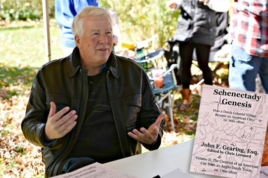 "Author John Gearing talks to an attendee during the Mabee Farm Arts Festival in Rotterdam Junction on Sunday. Inset: Volume II of ""Schenectady Genesis."" (Stan Hudy/Staff Writer)"