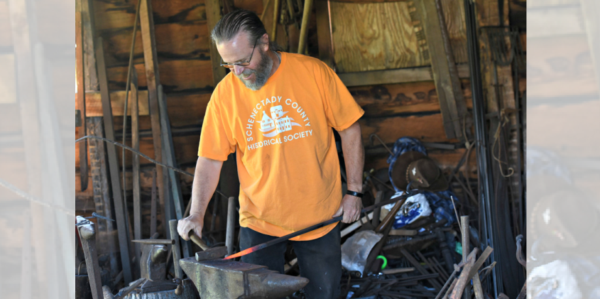 Schenectady County Historical Society facilities manager and blacksmith John Ackner works a piece of steel, shaping it into a fireplace poker, demonstrating the skill during the Mabee Farm Arts Festival in Rotterdam Sunday