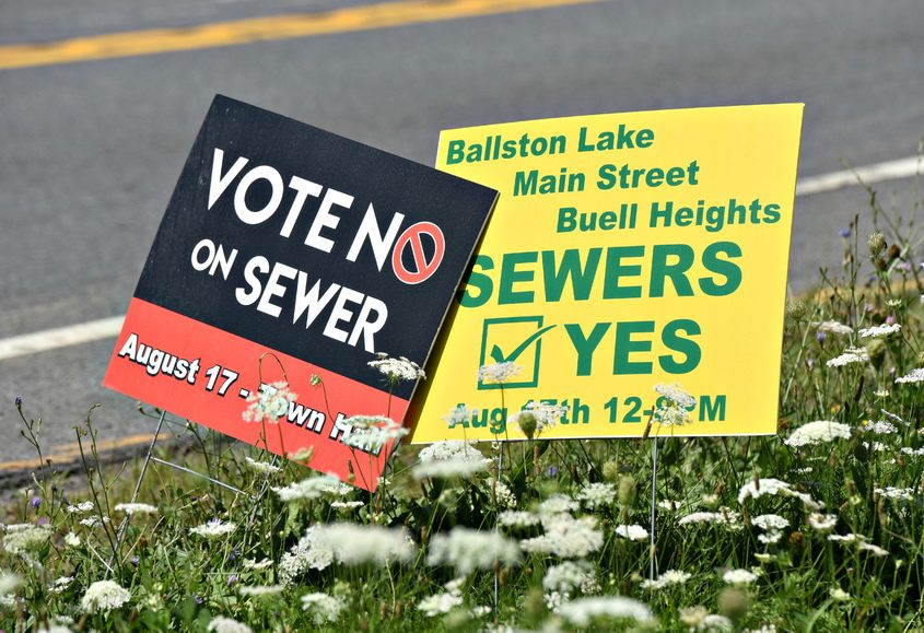 Dueling sewer project signs adjacent to each other at the corner of Midline Road and Route 50 in Burnt Hills. Residents will vote on the project on Aug. 17, 2020 at the town hall. Aug. 5, 2020.