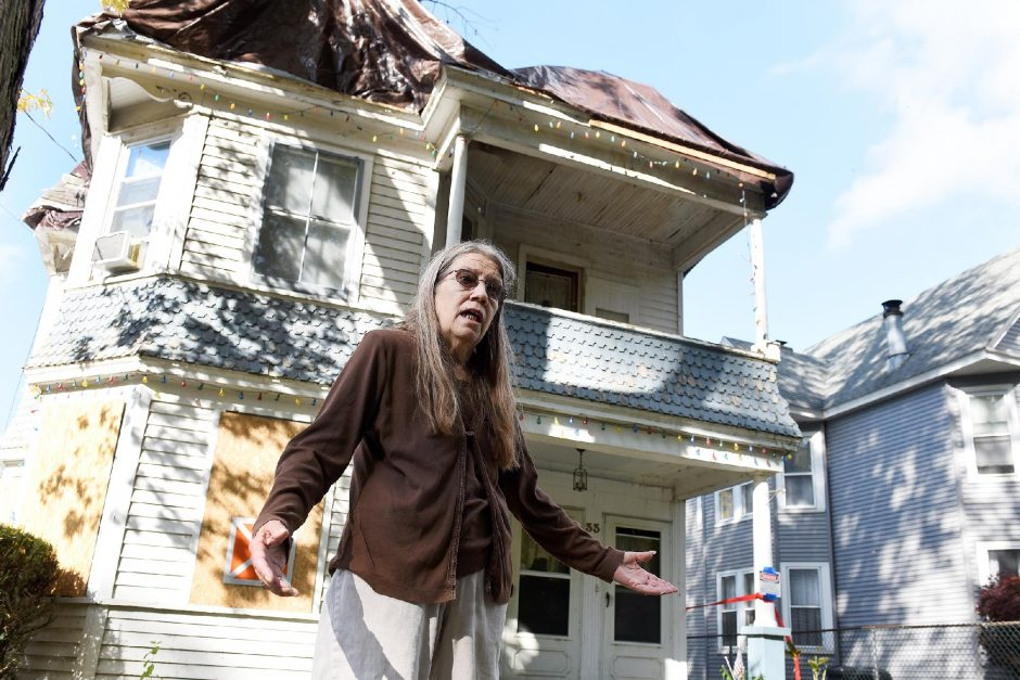 ERICA MILLER/STAFF PHOTOGRAPHER Linda Gibbons stands in front of her house at 33 Washington Ave. in Scotia on Friday. The house, which burned on Labor Day weekend, is tarped and condemned. Neighbors say lack of water hindered firefighting efforts.