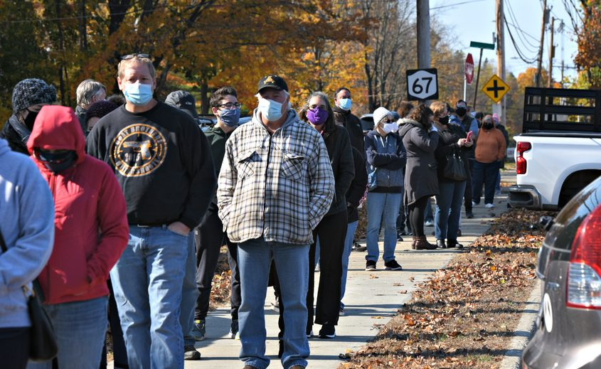 STAN HUDY/STAFF WRITERVoters stand on the sidewalk on West High Street and around the corner on McMaster Street in Ballston Spa Sunday afternoon during the second day of early voting in New York State.