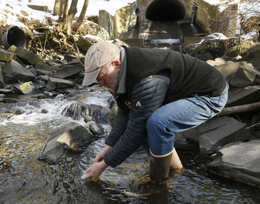 Union College Professor John Garver takes a water sample from the Hans Groot Kill on campus.