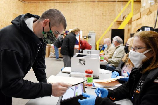 ERICA MILLER/STAFF PHOTOGRAPHER Chris Miller of Johnstown signs in before casting his ballot with the help of inspector Mary Mosetti during early voting in Johnstown on Monday.