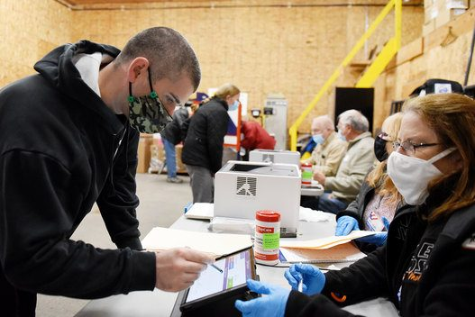Chris Miller, of Johnstown, signs in before casting his ballot with the help of inspector Mary Mosetti, of Perth, during early voting at Fulton County garage in Johnstown on Monday, October 26, 2020.
