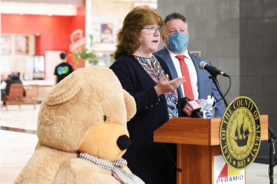 Albany County Executive Daniel McCoy listens Monday at Crossgates Mall as Albany County Department for Children, Youth and Families Commissioner Moira Manning announces details of theAdopt-A-Family holiday program. (Erica Miller/Staff Photographer)