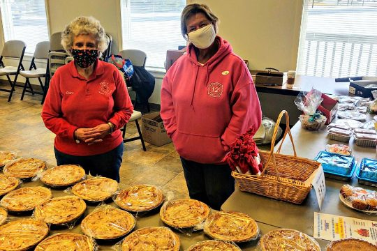 Elaine Gasner (left) and Linda Swietlicki of the Perth Volunteer Ladies Auxilary offer several tables of take home sweets Tuesday afternoon inside the Perth Municipal Complex and District 1 and 2 voting precinct on election day. Nov. 3, 2020. (STAN HUDY/STAFF WRITER)