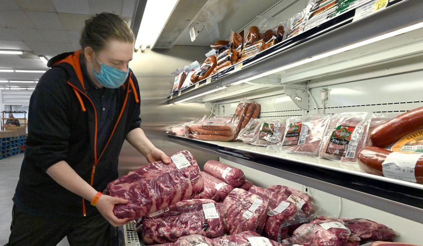 Ian Hadley stocks the meat coolers at Master Deli Marketplace in Broadalbin in April. Credit: Marc Schultz/Staff Photographer