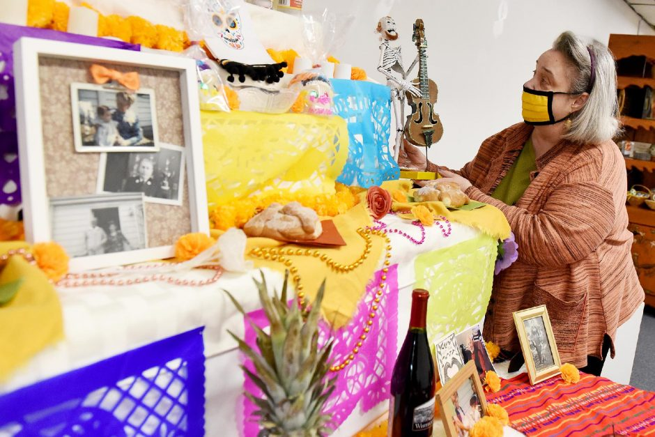 ERICA MILLER/STAFF PHOTOGRAPHER New York Folklore gallery manager Laurie Longfield adjusts the display for their Mexican Day of the Dead (El Dia de los Muertos)at the gallery on Jay Street in Schenectady on Thursday. The display will be upuntilSunday.